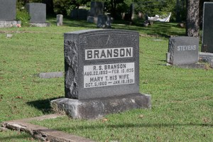The gravestone of Ruben Bransonis readily visible driving by the NW corner of Oklahoma and Commercial Steets in historic downtown Branson.