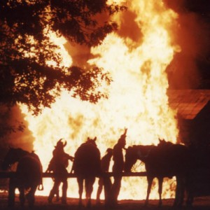 "Scene from the ""Shepherd of the Hills Outdoor Drama"" with the  Bald Knobbers burning cabin. Notice the outline of their distinctive masks."